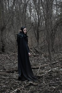 Lossien standing in a dead forest, with a long black wig and elf ears, facing mostly away from camera. She is wearing a long trailing black cape and a black feathered mantle.