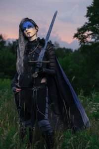 Lossien standing in a field at sunset, wearing a Yasha costume. She has long grey hair swept to one side, and a black and grey costume with a blue cape. Her face is blue on the top half. One hand is hooked in her belt, and the other holds a large sword over her shoulder.