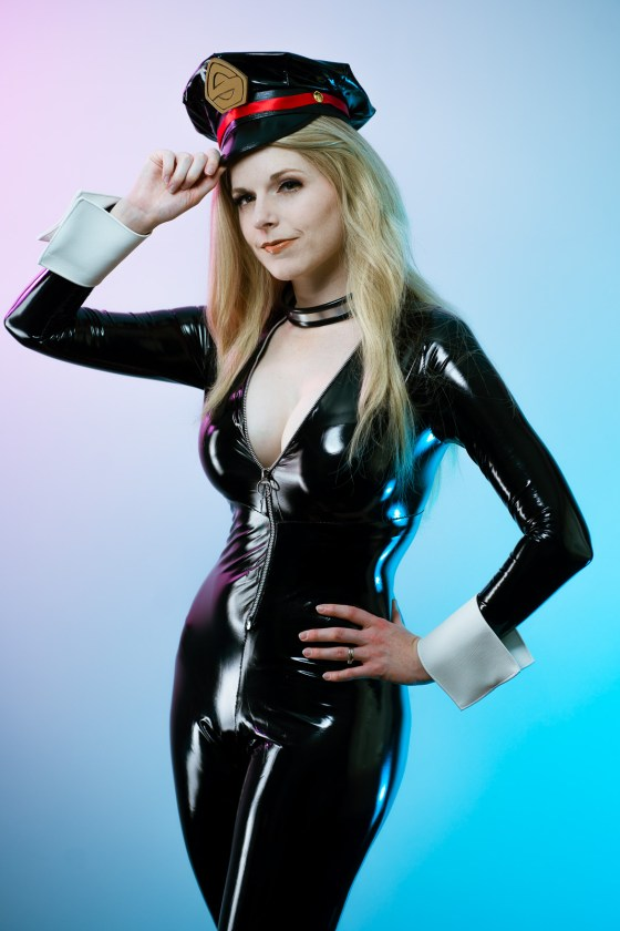 Lossien in a PVC catsuit, with a matching hat. She has blonde hair, and is holding one hand up to the hat while the other rests on her hip. The background is pink in the top left corner and shift into a blue in the bottom right.