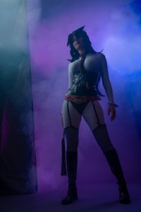 Lossien standing as Lady Midnight, wearing a white bodysuit, with a black PVC corset and underpants. She is also wearing purple thigh highs, and a long black wig. She is standing in front of a foggy purple background.