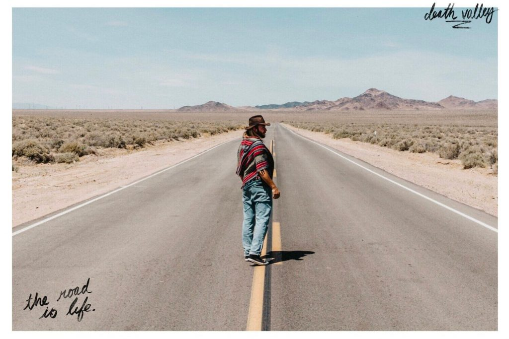 About Lost Boy Memoirs photo of a male in jeans and a red poncho walking down a desert highway alone with mountains in the distance.