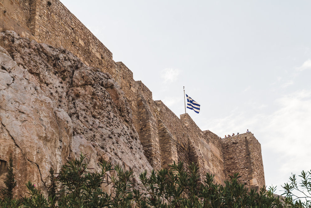 A photo of The Acropolis of Athens with Greek Flag blowing in the wind.