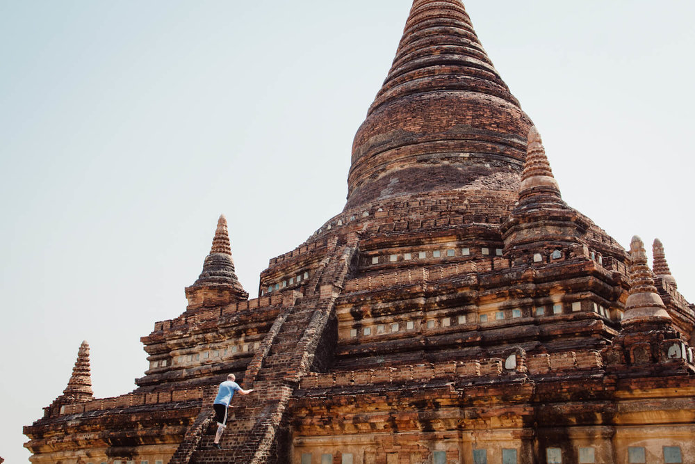 A photo of a man climbing the temples in Bagan Myanmar.