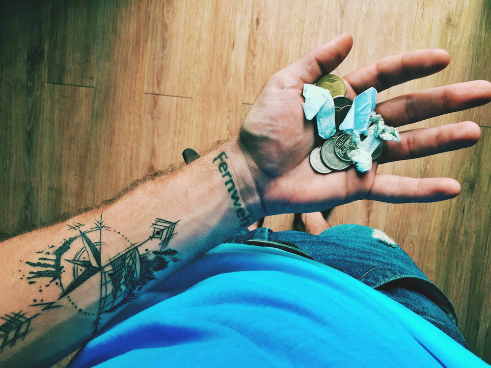 A Photo of change and lint in an open palm showing Thai Baht and being broke, with Ryan's tattoos of Fernweh and the compass and globe in view.