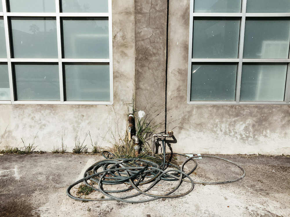 Lost in Los Angeles Photo Series: Photo of a tangled and coiled hose against a concrete wall.