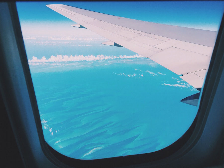 Photo of Airplane wing over the bright blue caribbean sea.