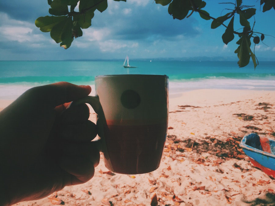 Ile A Vache island in Haiti, drinking a fresh brewed cup of coffee on the beach with a sailboat in the distance.