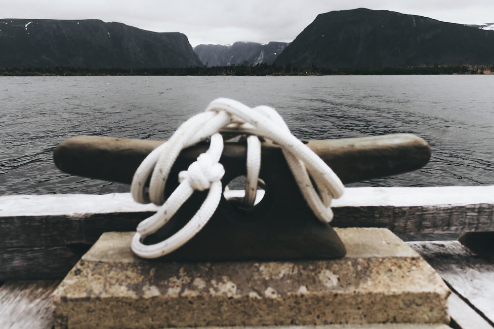 Photo of Gros Morne Nation Park in northeastern Canada. A boat cleat with an oxo rope tied on a pier overlooking a dark bay and Gros Morne Fjord.