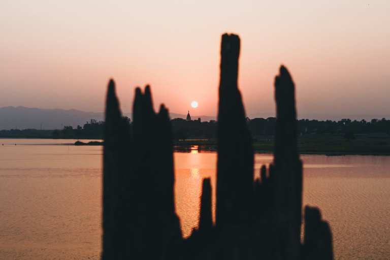 Photo from Ubein Bridge, a Unesco World Heritage site in Myanmar, and the oldest and longest teak wood bridge in the world. Photo from Ubein Bridge, a Unesco World Heritage site in Myanmar, and the oldest and longest teak wood bridge in the world. A pink and orange sunrise reflects off of the calm water of Taungthaman Lake near Amarapura and silhouettes of boats and trees. #Myanmar #Burma #Travel #Photography #Asia