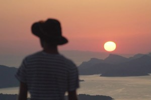 Epic Travel Moments photo for cinematic travel and adventure reel showing a silhouette of a male watching a fiery sunset.