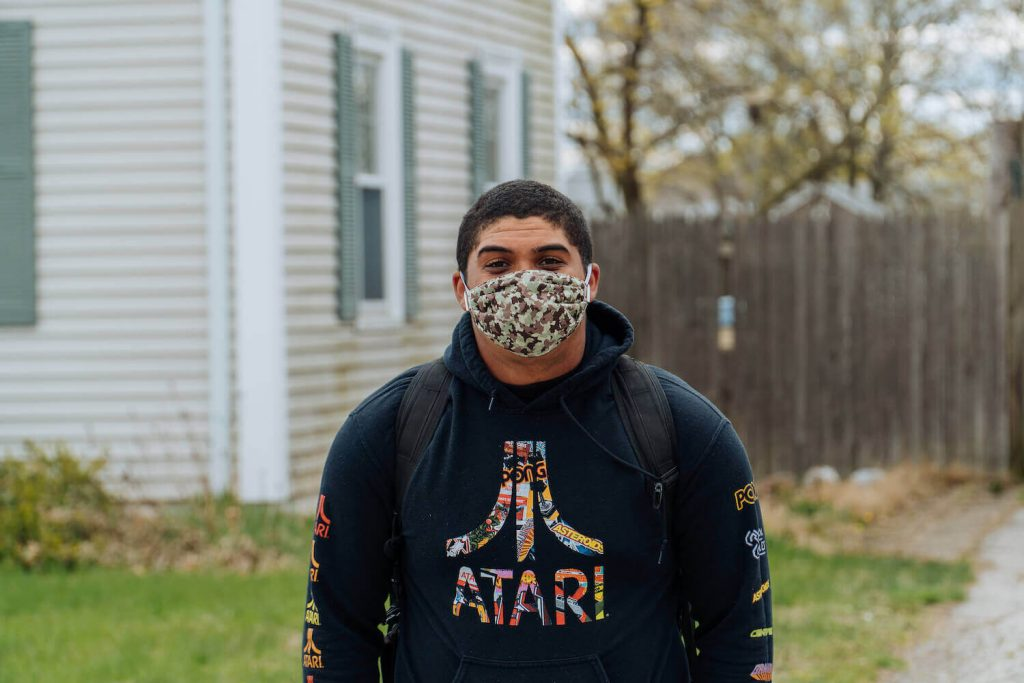 A photo of a male wearing a camouflage mask during covid-19 quarantine with an Atari sweater during Autumn.