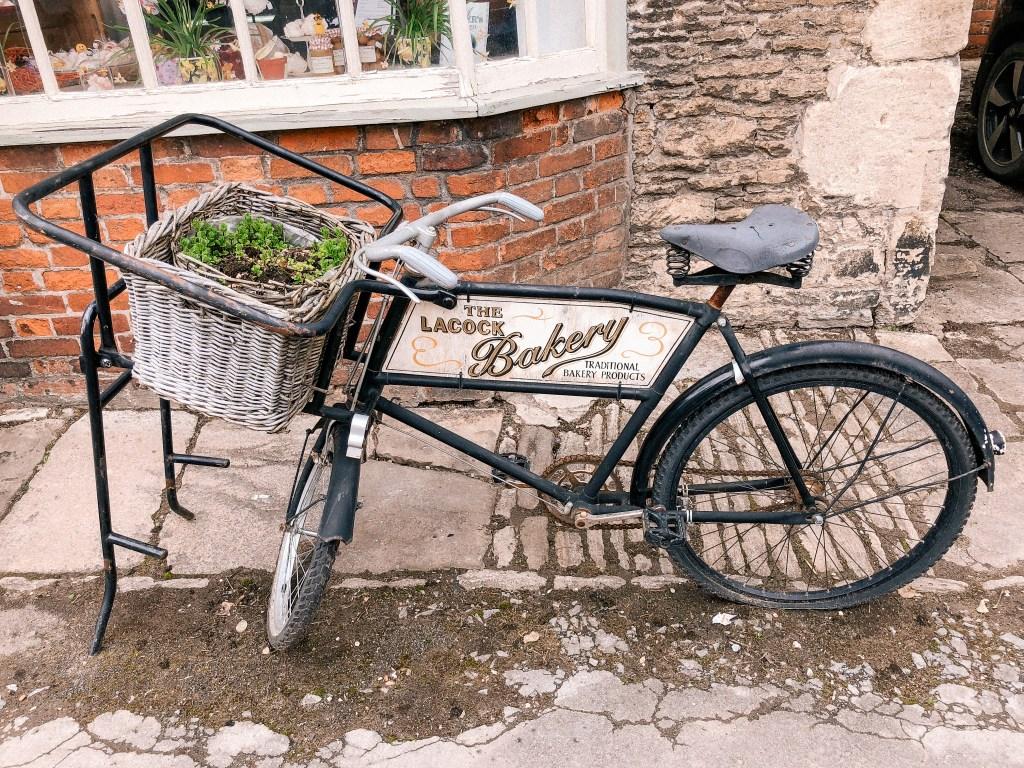 Lacock Bakery, Bike Planter, Lacock, Wiltshire, Cotswolds, UK, National Trust, England, English Countryside