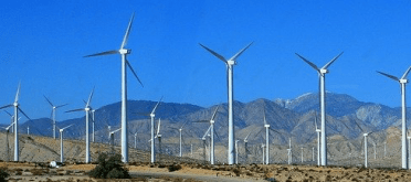 White tall windmills in Palm Springs California with a bright blue sky and mountains