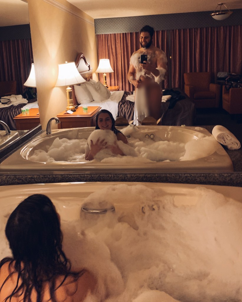 Cute and romantic couple stay at a hotel for a special occasion in a jacuzzi bathtub with bubbles