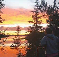 Young woman watching beautiful colourful sunset by a lake with trees