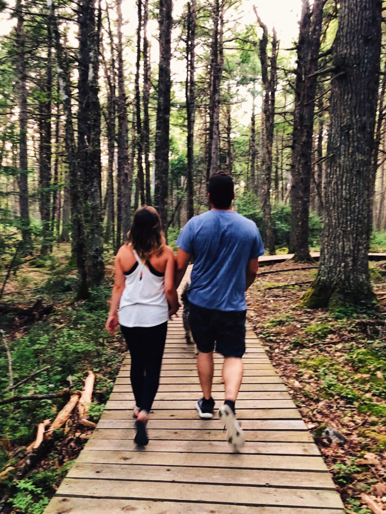 couple walking on trail holding hands surrounded by forest