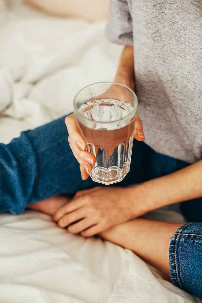 girl sits on bed drinking a glass of water