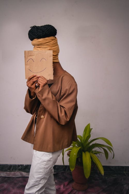 woman with mood disorder hold up a piece of cardboard in front of her face with a smile on it