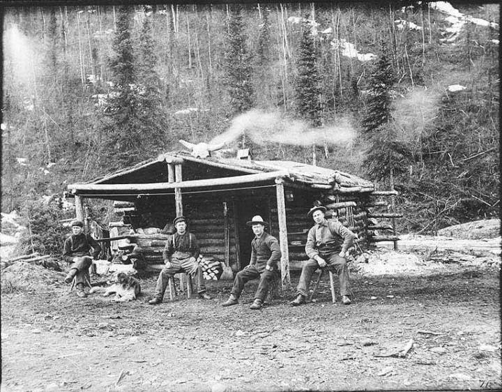 Four men and dog sitting in front of log cabin, Hunker Creek, 1899