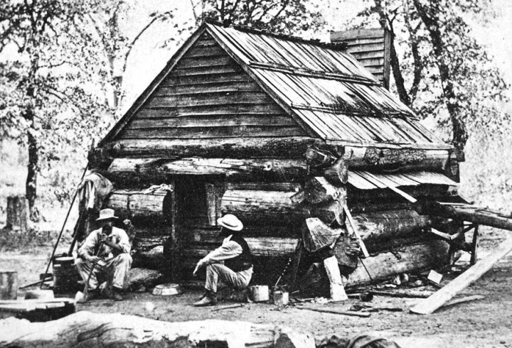 """Lamon's log cabin, the first built in Yosemite Valley, Calif."" Their work completed, two men sit on stumps in front of the finished product, ca. 1895."