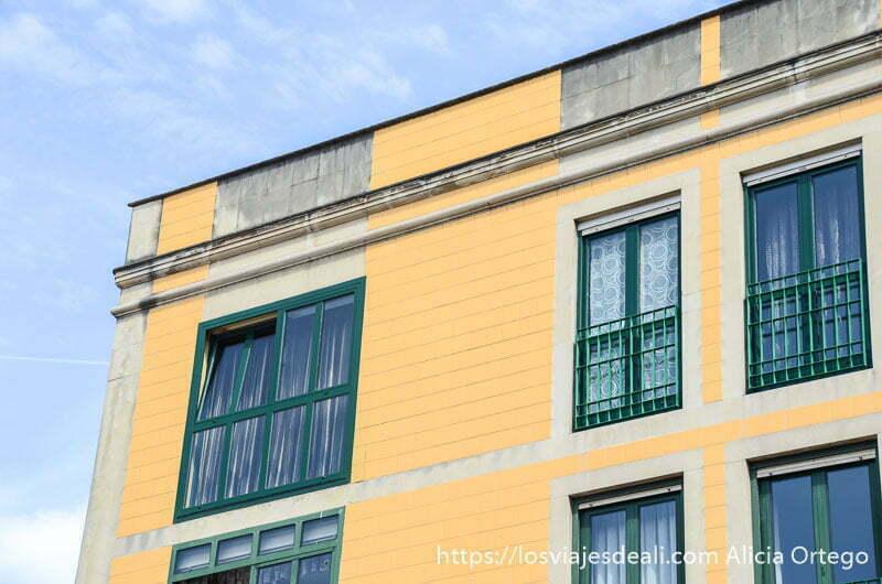 edificio amarillo con ventanas y balcones verdes