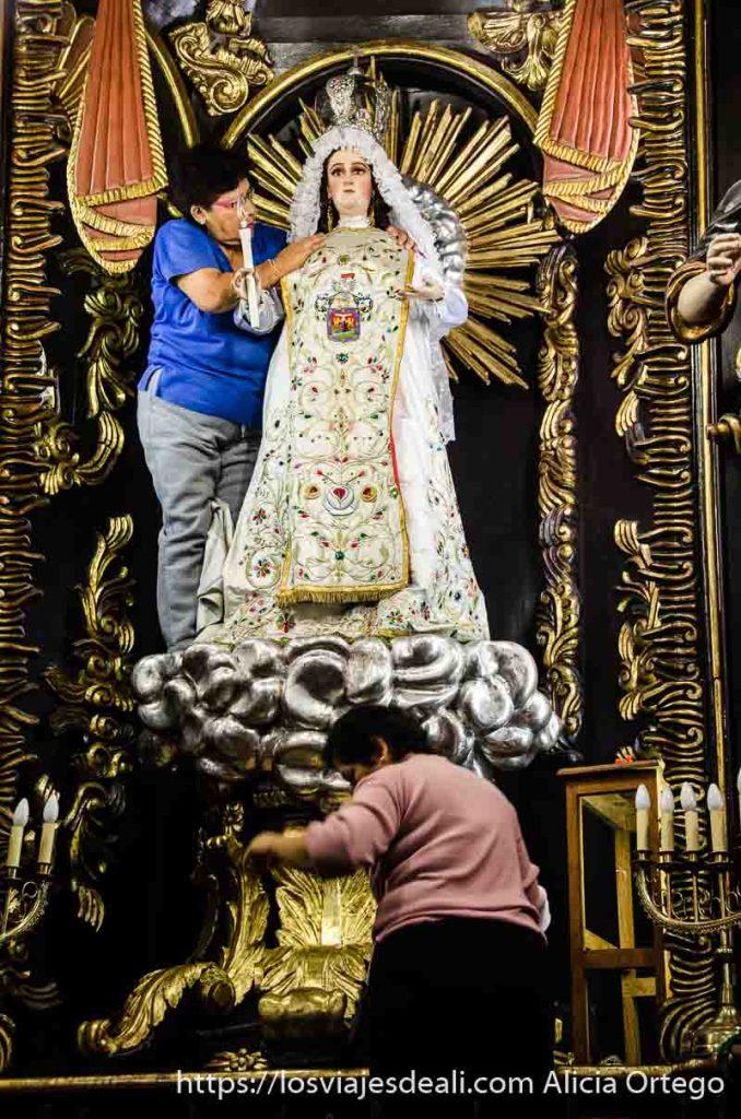 dos mujeres arreglando a una virgen con vestido blanco