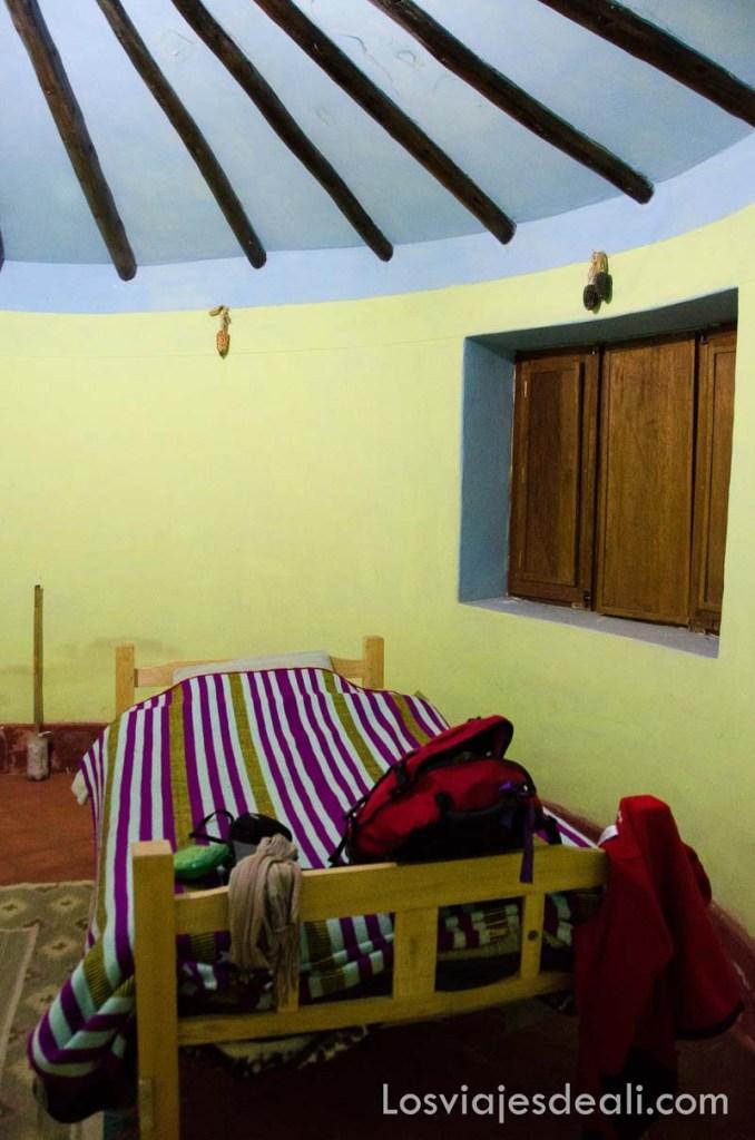 habitación circular con cama individual y manta a rayas
