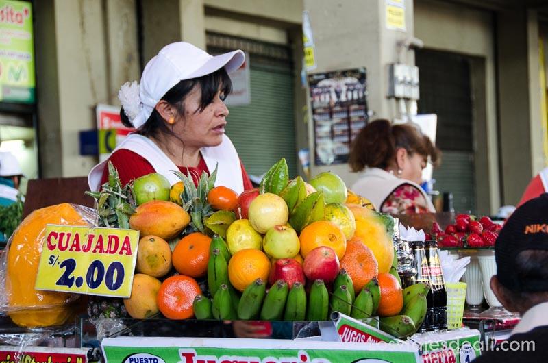 mujer detrás de un montón de frutas en el mercado de san camilo de arequipa