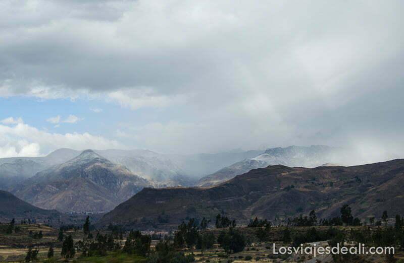 paisaje de montañas con nubes y rayos de sol atravesándolas