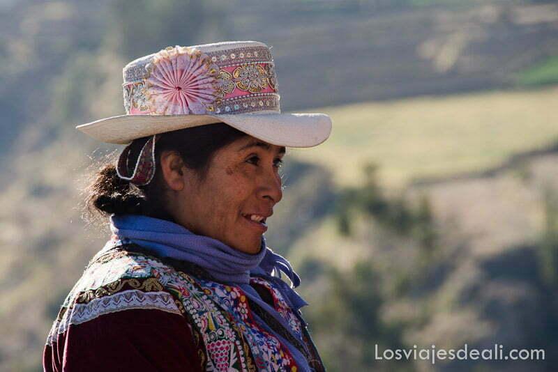 mujer indígena con sombrero de ala ancha sonriente en el cañón del colca