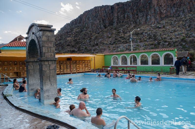 turistas bañándose en piscina de aguas termales