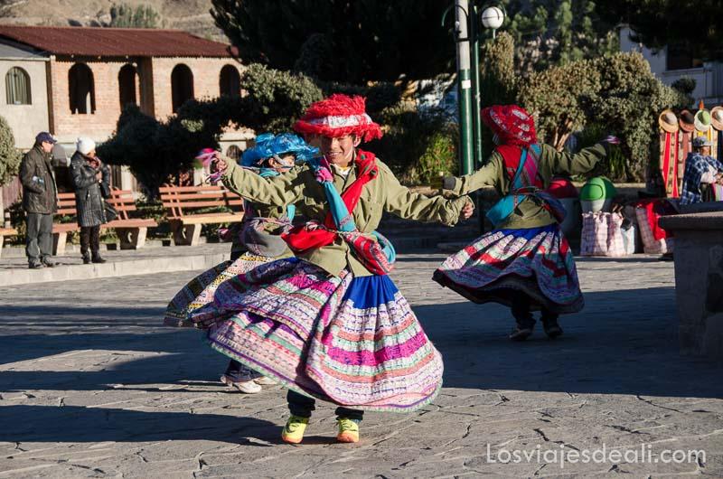 jóvenes de uno de los pueblos del valle del colca con faldas bordadas bailando en la plaza