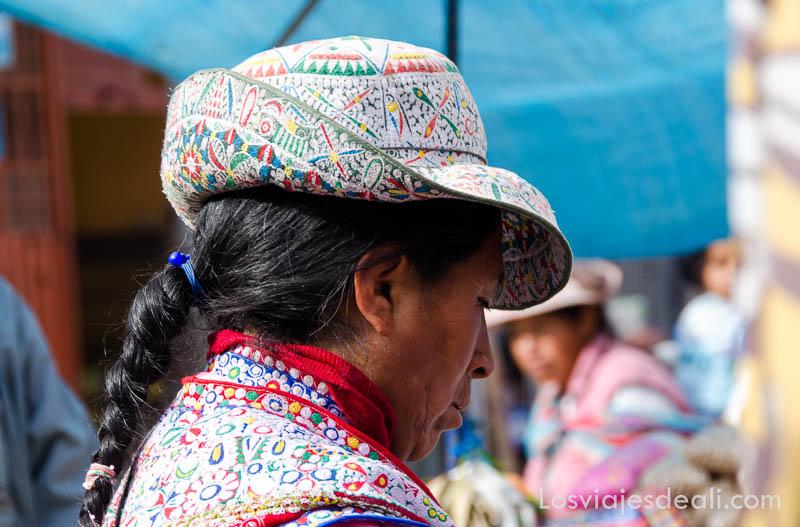 mujer con gorro bordado de colores y trenza negra