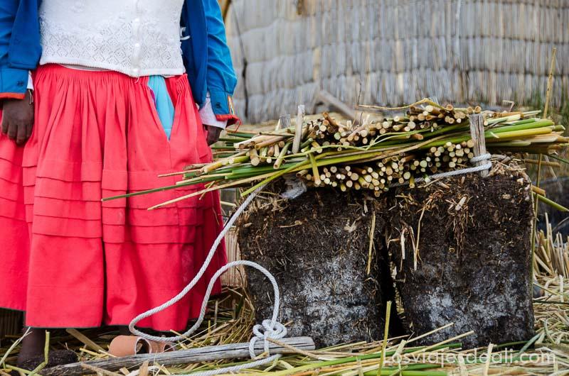 mujer con falda roja y pieza de tierra y totora para explicación de construcción