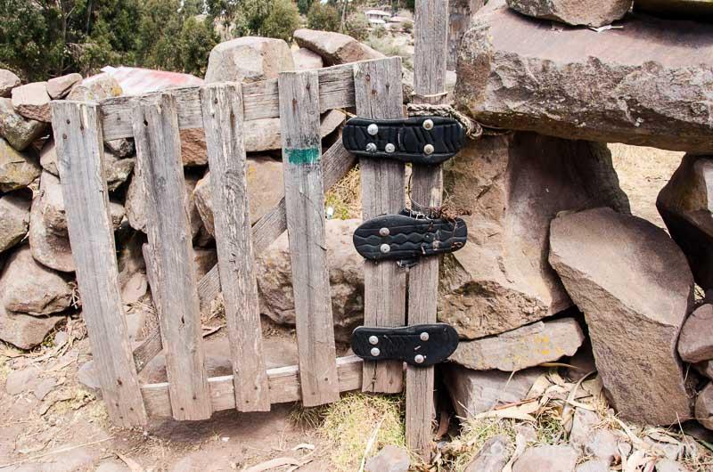 puerta de cerca de madera cuyas bisagras son suelas de goma de zapatillas