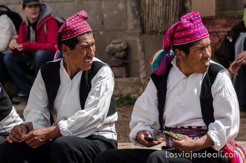 dos hombres con camisa blanca chaleco negro y gorros de lana de rayas rosas y negras