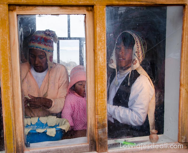 una chica un chico y una niña preparando desayuno a base de tortitas mientras miran por la ventana