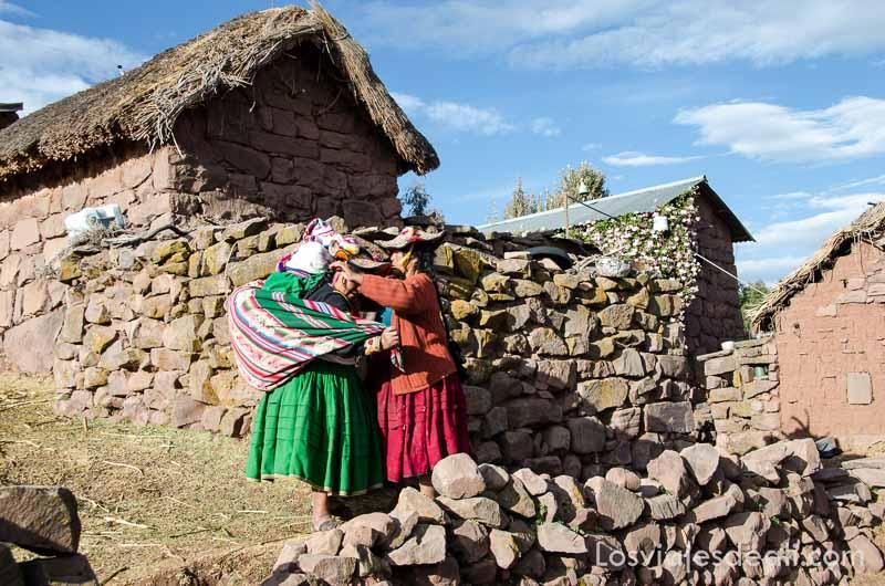 una mujer colocando bebé en la espalda de otra junto a valla de piedra en la Península de Capachica