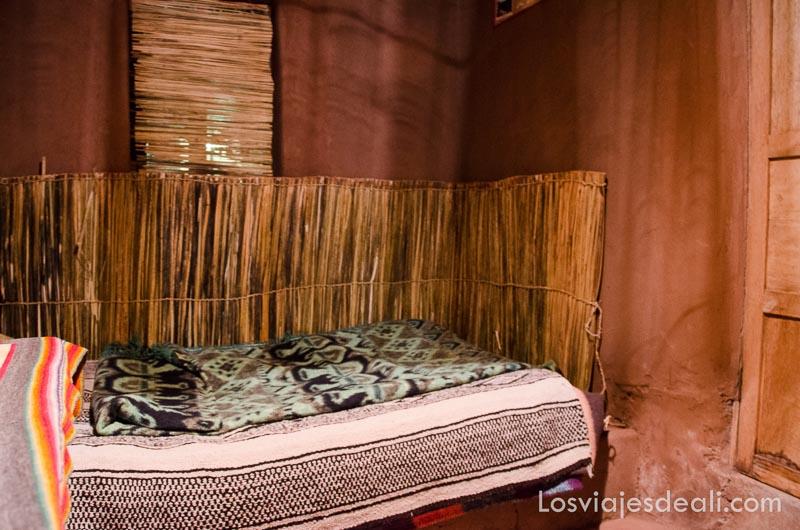 cama con mantas de lana en habitación de adobe