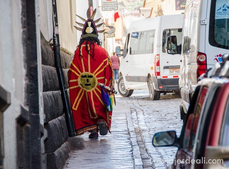 hombre disfrazado de inca con capa roja y sol bordado en ella anda por una calle de cuzco
