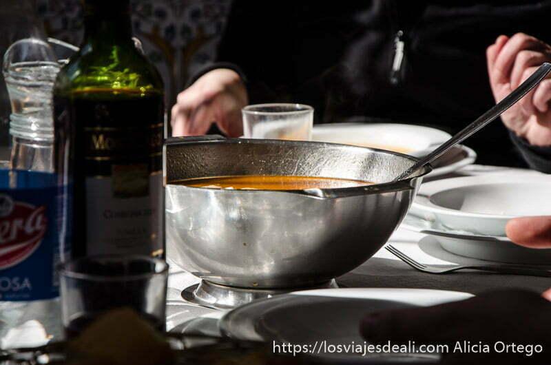 perol lleno de sopa de cocido y botella de vino