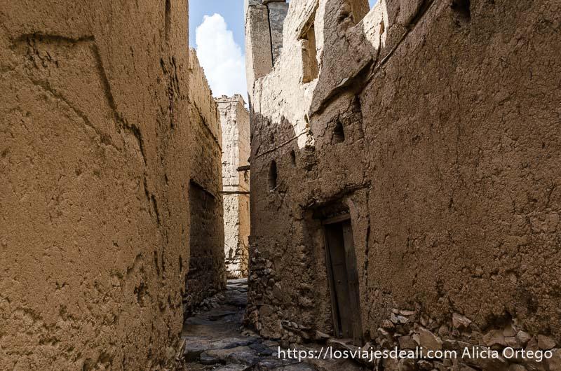 calle estrecha con casas de adobe y puertas de madera en un pueblo de las montañas de omán
