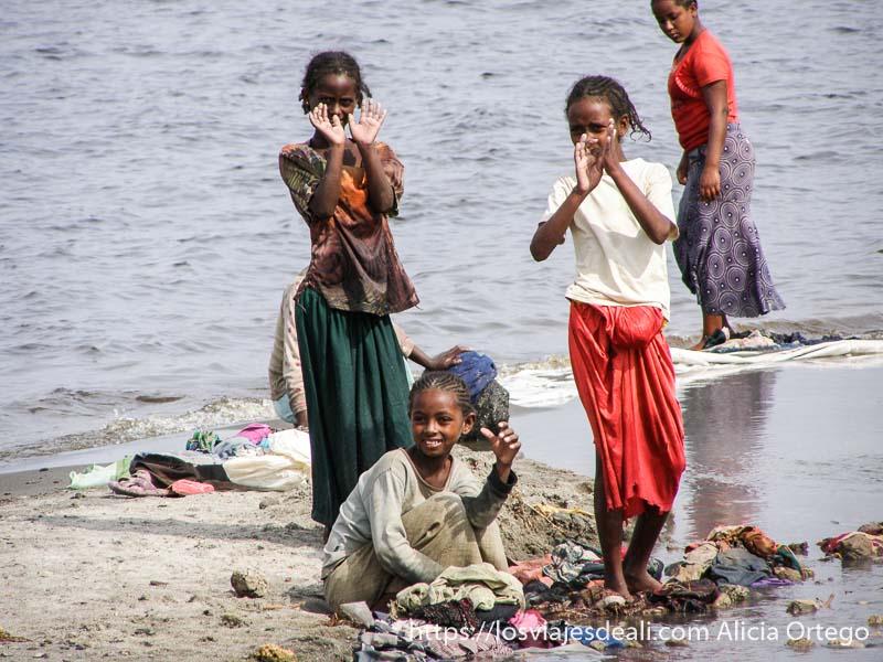tres niñas etíopes muy delgadas lavando ropa junto al lago chitu en etiopía