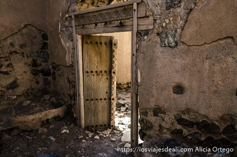 muro en ruinas con puerta de madera labrada entreabierta en un oasis de omán