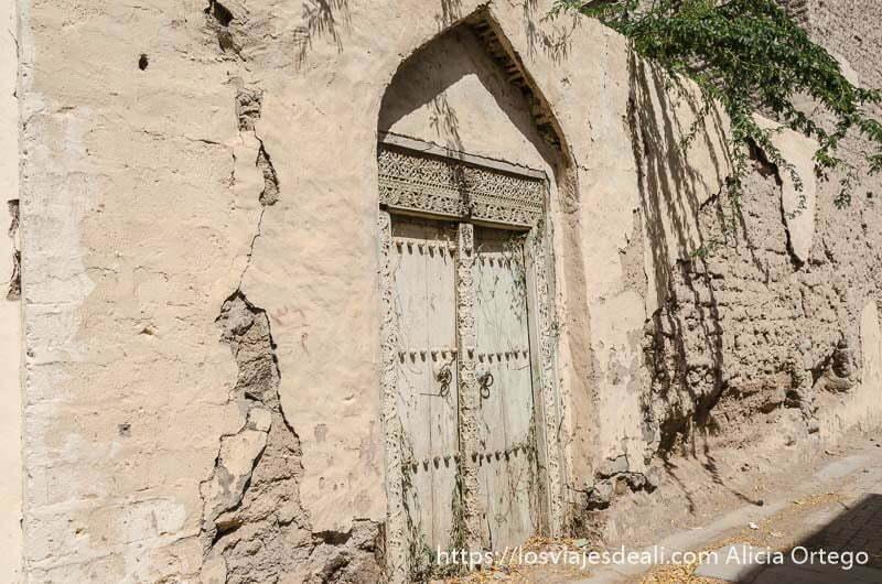 puerta de madera labrada al estilo de india en muro de adobe