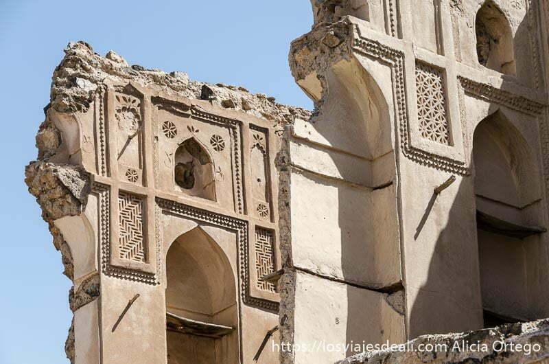 muro en ruinas con revestimiento interior de adobe con arcos y huecos para usar de estantería