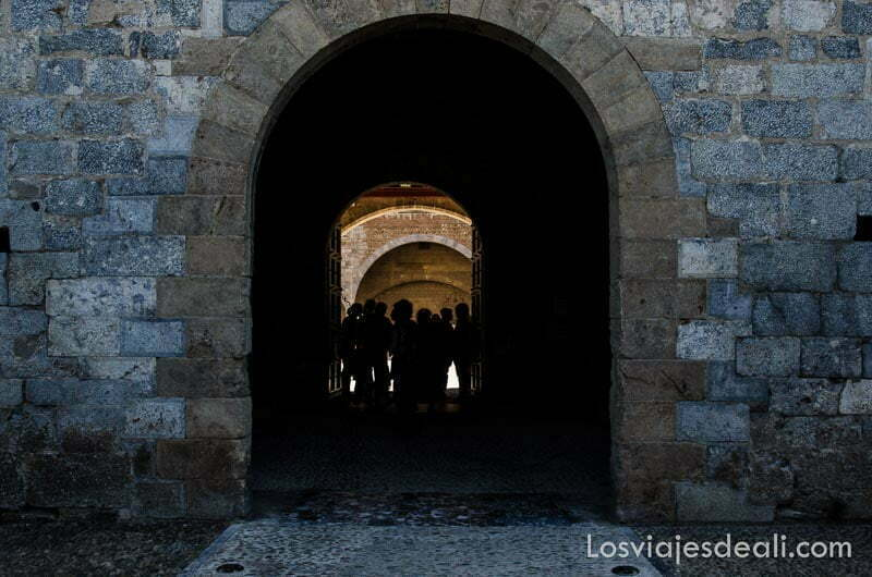 grupo de gente entrando por puerta en forma de arco en castillo