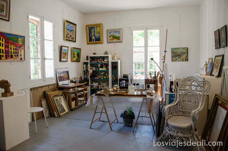 taller de pintor en habitación iluminada con muchos cuadros
