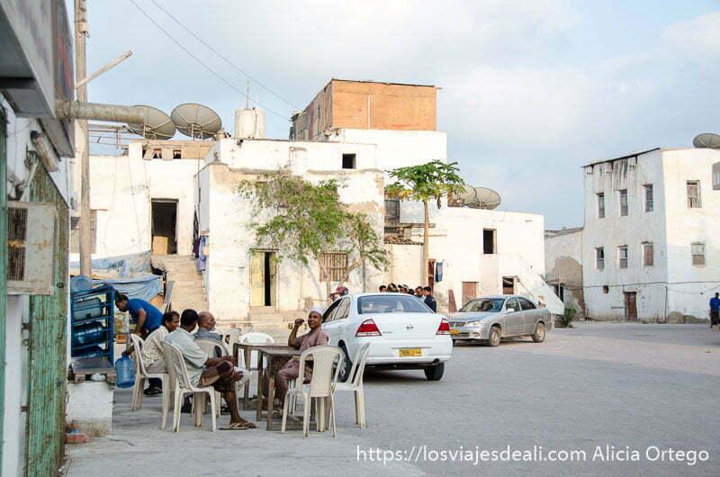 grupo de hombres sentados en sillas de plástico en una plaza con edificios blancos alrededor