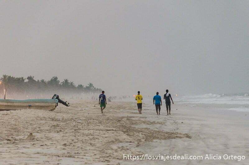 chicos andando por la playa de salalah con una barca en la arena y palmeras al fondo